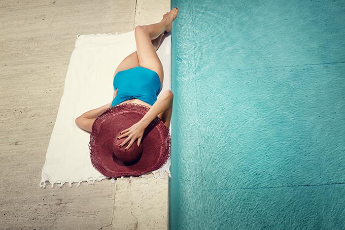 Frau am Pool mit Badeanzug